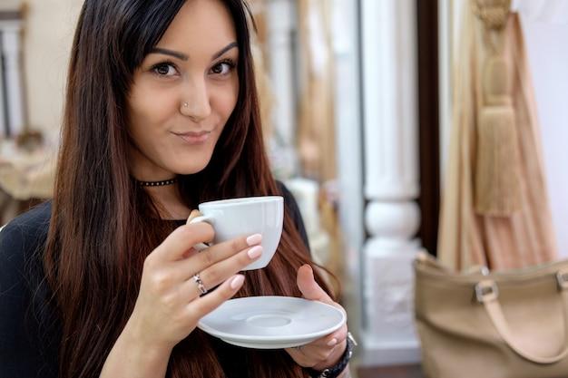 Mujer morena tomando café en la cafetería