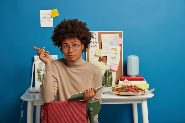 Mujer morena vacilante escribe un artículo en un cuaderno, toma nota de los planes con expresión inconsciente, lleva gafas transparentes y cuello alto beige