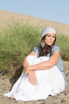 Mujer morena con velo en las dunas del desierto