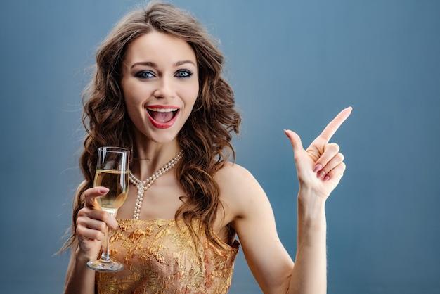 Mujer morena con vestido dorado y collar de perlas con copa de champán levantada celebra