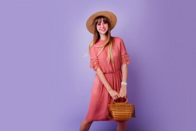 Mujer morena en vestido rosa de moda y sombrero de paja con bolsa de bambú en violeta.