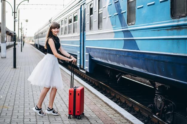 Mujer morena viajero con maleta roja caminando en la estación de ferrocarril