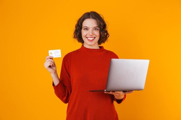 Mujer morena vistiendo un suéter con un portátil plateado y una tarjeta de crédito mientras está de pie aislado en amarillo