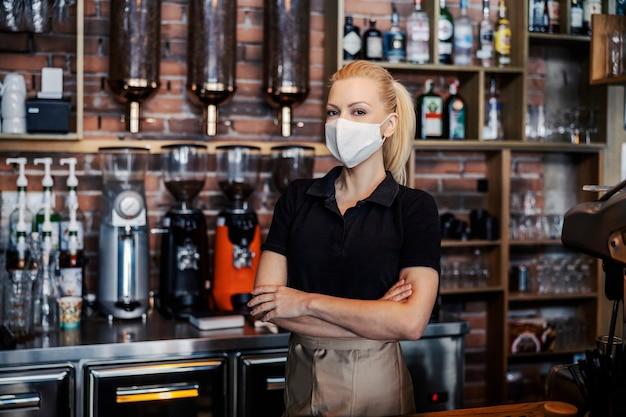 La mujer se para en el mostrador del restaurante y viste una camiseta negra y un delantal.