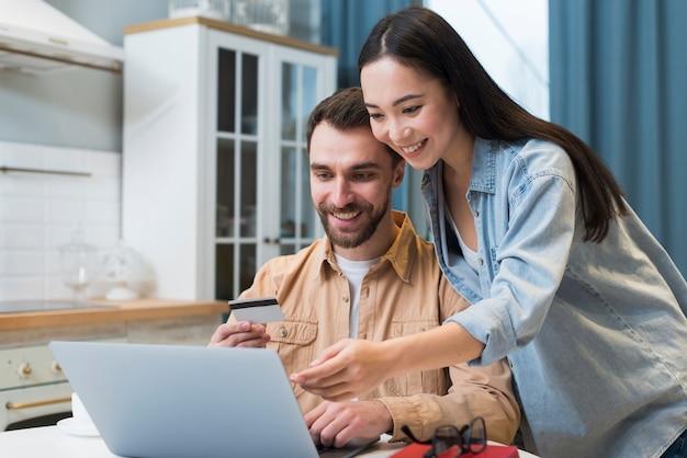 Mujer mostrando al hombre en la computadora portátil lo que quiere comprar en línea
