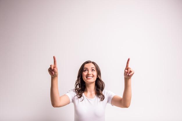 La mujer está mostrando y apuntando al lado en el espacio de la copia en blanco.