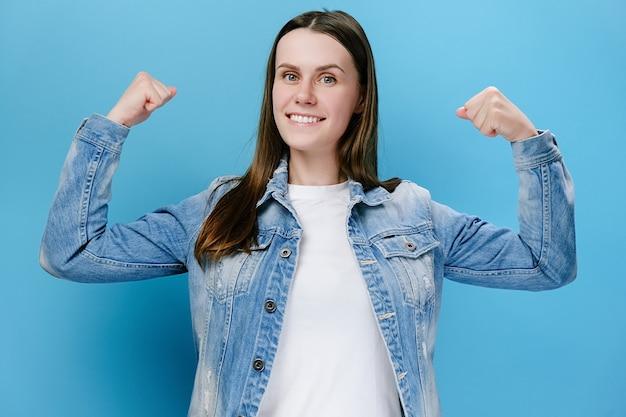 Mujer mostrando bíceps y mirando confiado