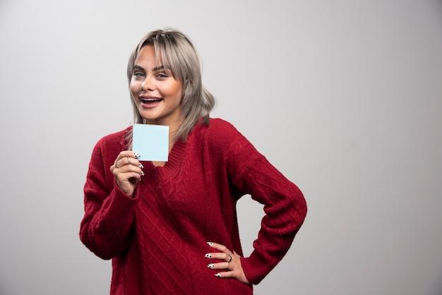Mujer mostrando bloc de notas sobre fondo gris.