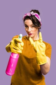 Mujer mostrando cuernos de diablo y un spray de casa