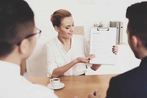 Mujer está mostrando curriculum vitae en entrevista de trabajo