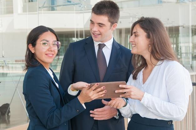 Mujer mostrando datos de colegas en tableta, mirando a cámara