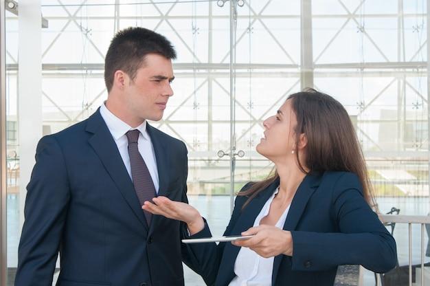 Mujer mostrando datos de hombre en tableta, discutiendo