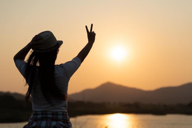 Mujer mostrando dos dedos o gesto de victoria durante el atardecer, sentirse motivado