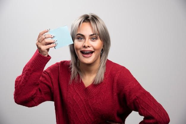 Mujer mostrando felizmente el bloc de notas sobre fondo gris.