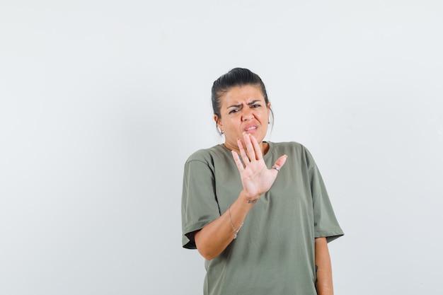 Mujer mostrando gesto de parada en camiseta y mirando molesto
