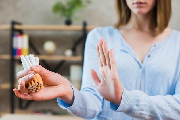 Mujer mostrando gesto de parada sosteniendo manojo de cigarrillos en la mano