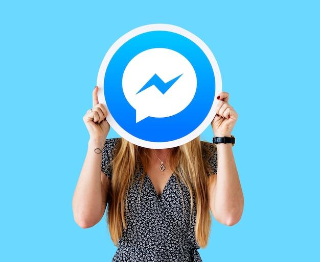 Mujer mostrando un ícono de facebook messenger