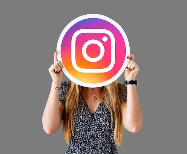 Mujer mostrando un ícono de instagram