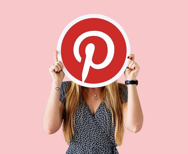 Mujer mostrando un ícono de pinterest