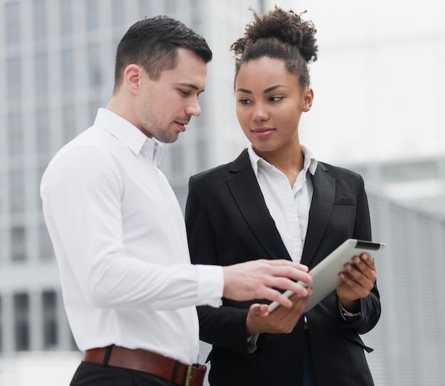Mujer mostrando ipad a colega