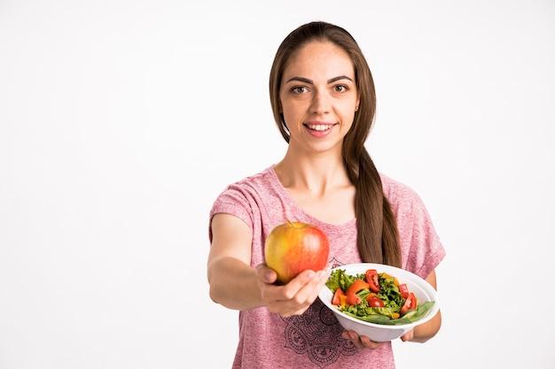 Mujer mostrando una manzana y sosteniendo una ensalada