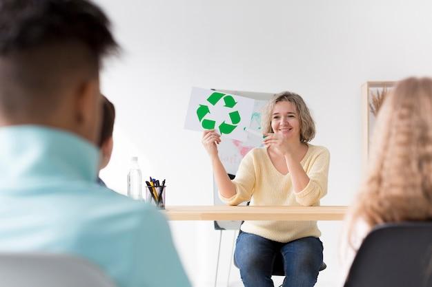 Mujer mostrando a los niños reciclar signo