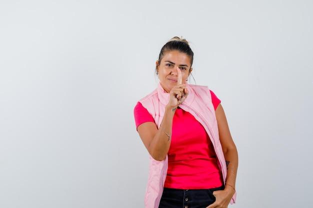 Mujer mostrando el número uno con el dedo en camiseta, chaleco y mirando sensible