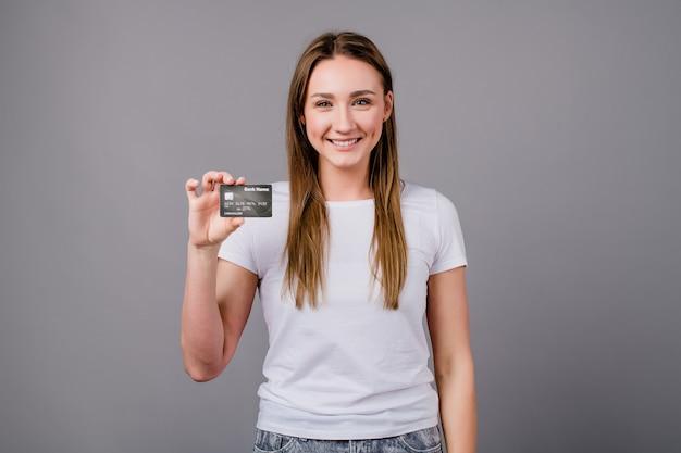 Mujer mostrando plantilla de tarjeta de crédito y sonriendo aislado en gris