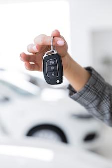 Mujer mostrando primer plano de las llaves del coche