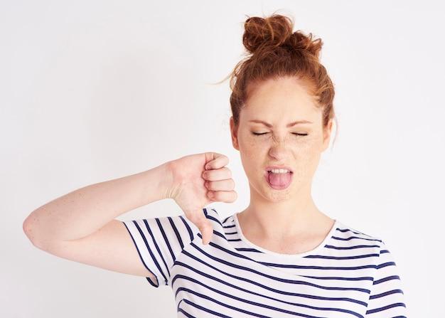 Mujer mostrando el pulgar hacia abajo y haciendo muecas shot