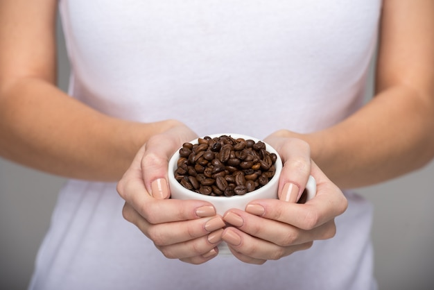 La mujer está mostrando puñado de granos de café tostado.