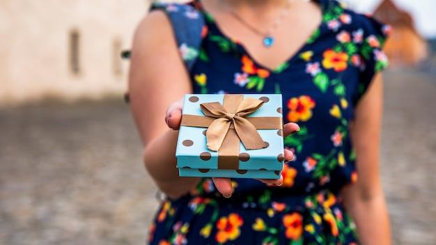 Mujer mostrando regalo en la calle.
