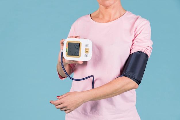 Mujer mostrando resultados de presión arterial en pantalla de tonómetro eléctrico.