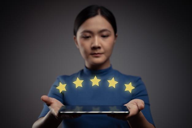Mujer mostrando retroalimentación presente de tableta, reseñas con efecto de holograma de icono de cinco estrellas