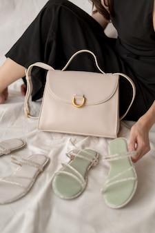 Mujer mostrando sandalias y bolsos de cuero