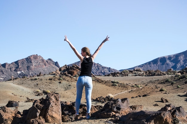 Mujer mostrando el signo de la paz con las manos en el aire