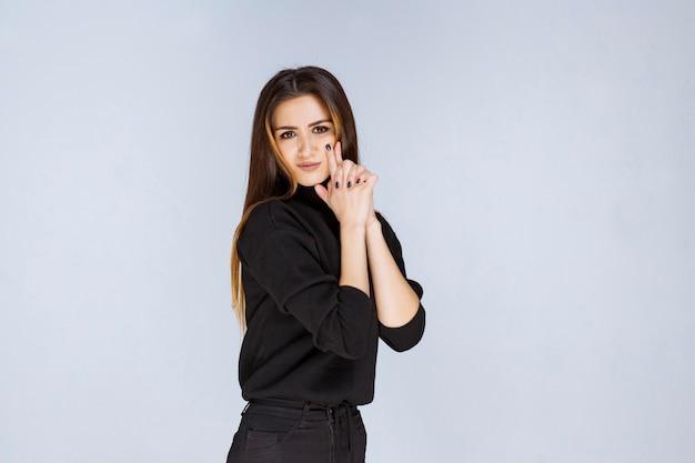 Mujer mostrando signo de pistola en la mano.