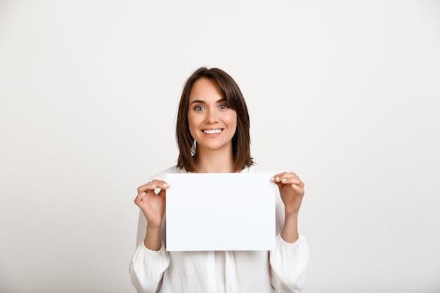 Mujer mostrando signos en papel blanco