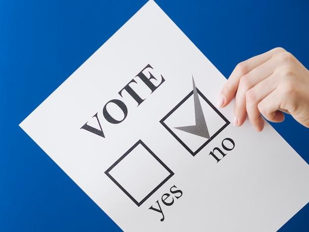 Mujer mostrando su elección en el referéndum con fondo azul.