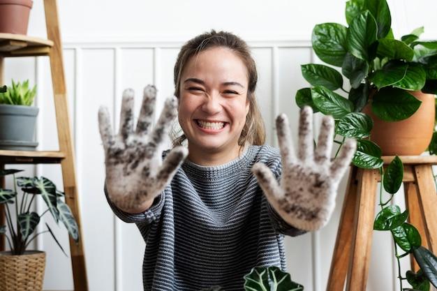 Mujer mostrando su guante de jardinería sucio