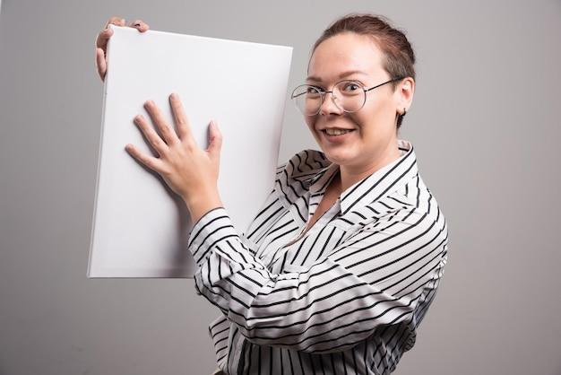 Mujer mostrando su lienzo blanco vacío sobre gris