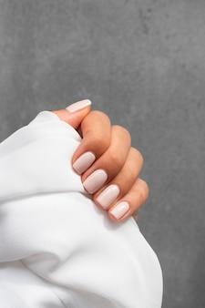 Mujer mostrando su manicura sobre un paño blanco