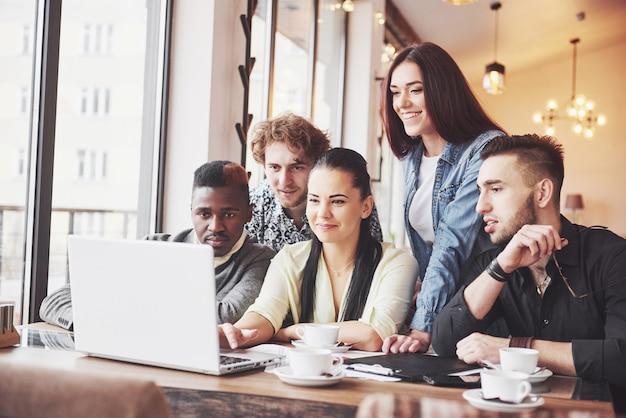 Mujer mostrando a sus compañeros de trabajo algo en la computadora portátil mientras se reúnen alrededor de una mesa de conferencias