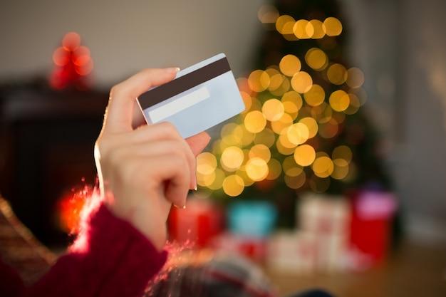 Mujer mostrando tarjeta de crédito en navidad