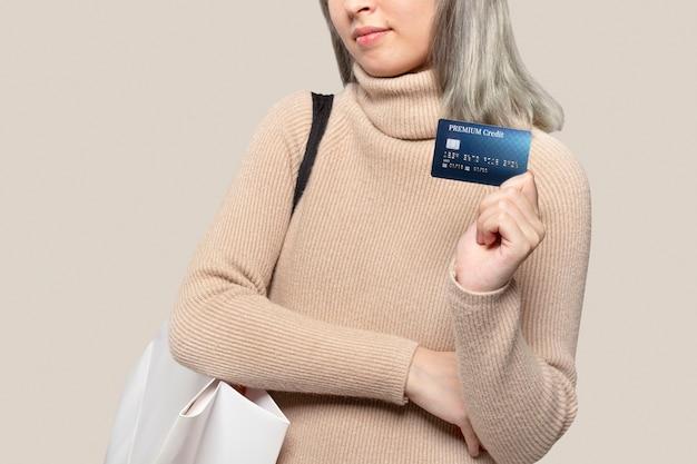 Mujer mostrando una tarjeta de crédito