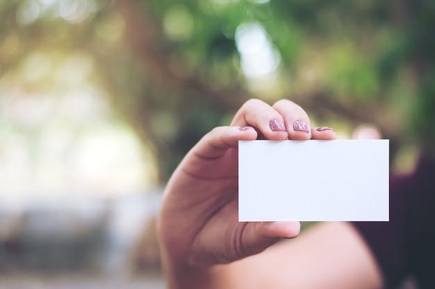 Mujer mostrando una tarjeta de negocios vacía