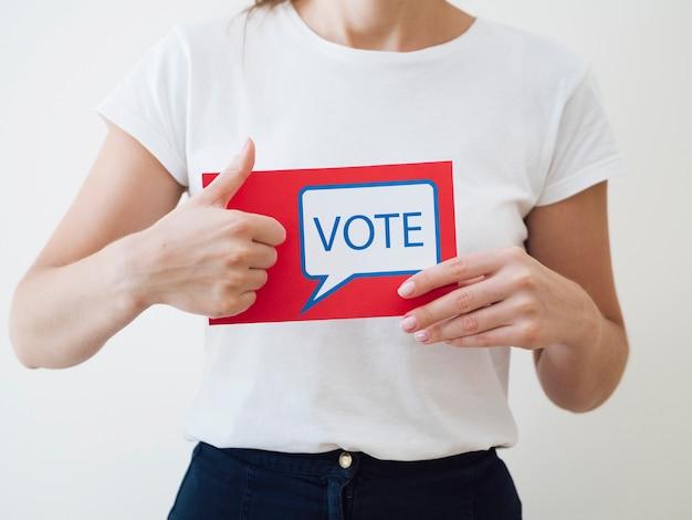 Mujer mostrando tarjeta roja con bocadillo de votación