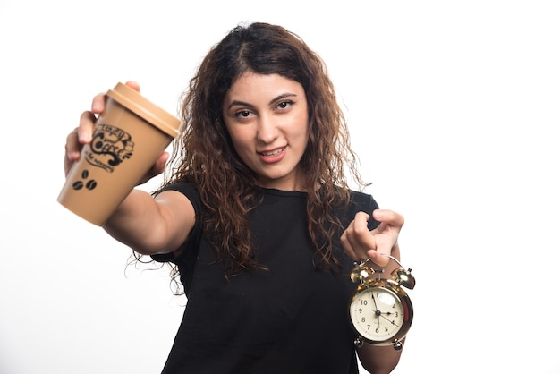 Mujer mostrando una taza de café con reloj sobre fondo blanco. foto de alta calidad