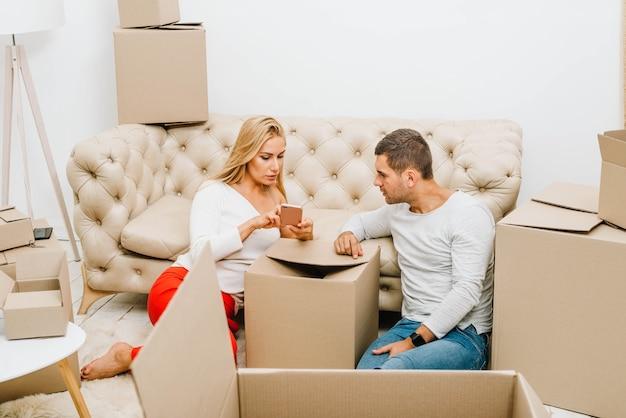 Mujer mostrando el teléfono al hombre mientras se muda