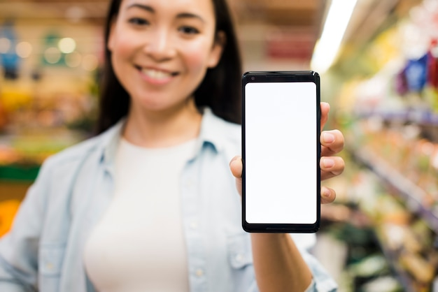 Mujer mostrando teléfono inteligente a la cámara en la tienda de comestibles